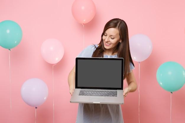 Ritratto di giovane donna sorridente attraente che indossa vestito blu che tiene il computer portatile del pc con lo schermo vuoto in bianco su fondo rosa pastello con gli aerostati di aria variopinti. concetto di festa di compleanno. Foto Premium