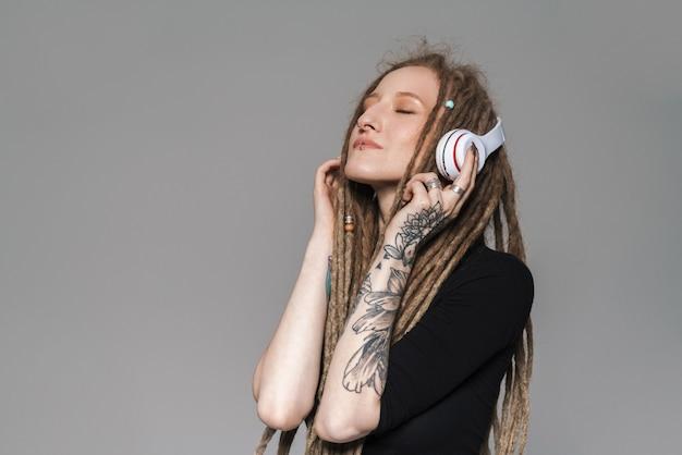 Ritratto di un'attraente giovane donna sorridente con i dreadlocks in piedi isolata, ascoltando musica con cuffie wireless