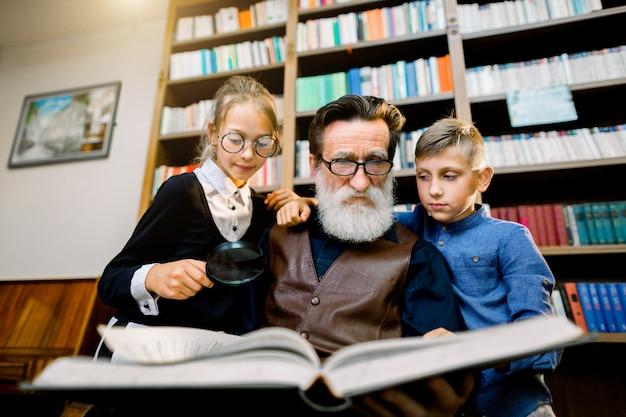 Ritratto di nipoti adolescenti attraenti e nonno barbuto anziano esperto che trascorrono del tempo insieme in biblioteca a leggere un libro interessante. libreria sullo sfondo