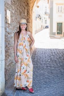 Ritratto di un'attraente donna turistica nella città vecchia indossando abiti lunghi alla moda, braccialetti e cappello di paglia.