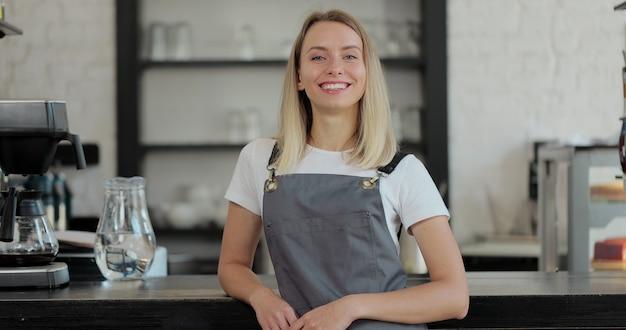 Ritratto di donna attraente bariata in piedi nell'apertura della caffetteria e sorridente che guarda l'obbiettivo. interno della caffetteria sullo sfondo.