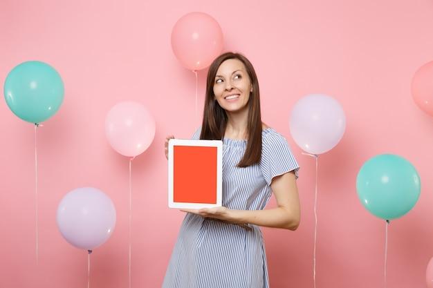 Ritratto di donna attraente in vestito blu che tiene computer tablet pc con schermo vuoto vuoto sognando guardando su sfondo rosa pastello con mongolfiere colorate. concetto di festa di compleanno.