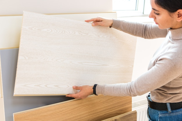 Ritratto di donna attraente nella costruzione di un negozio scegliendo la superficie in legno laminato per la ristrutturazione della casa e nuove idee di design.