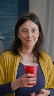 Ritratto di donna attraente che beve birra durante il fine settimana di celebrazione in un gruppo di fondo di multiet...