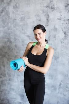 Ritratto di donna attraente tenendo blu yoga o stuoia di fitness dopo aver lavorato a casa