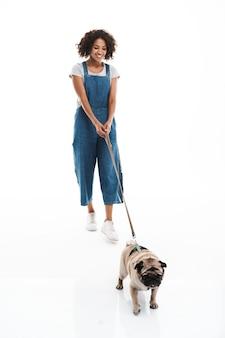 Ritratto di donna attraente che tiene il guinzaglio e cammina con il suo cane carlino isolato su un muro bianco