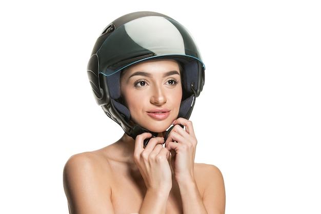 Ritratto di donna attraente in casco da moto sul muro bianco. concetto di bellezza, protezione della pelle e del viso