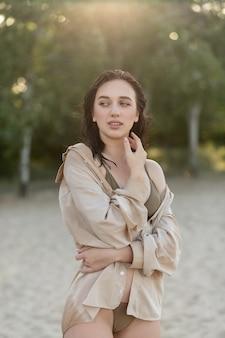 Ritratto di una donna attraente in piedi sulla spiaggia. la ragazza sorridente felice esamina la macchina fotografica al mare. giovane donna bionda che si rilassa in spiaggia