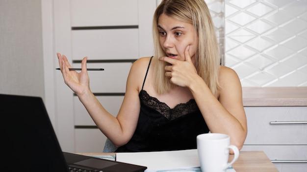 Ritratto di una donna attraente al tavolo con tazza e laptop