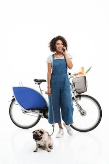 Ritratto di donna attraente che parla su smartphone mentre si trova in piedi con il suo carlino e la bicicletta isolati su un muro bianco