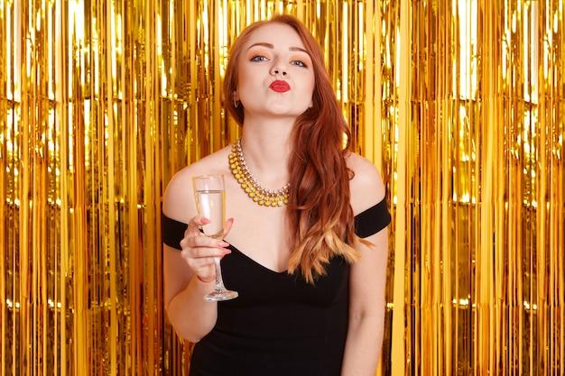 Ritratto di donna attraente che indossa un abito nero, bere champagne e celebrare