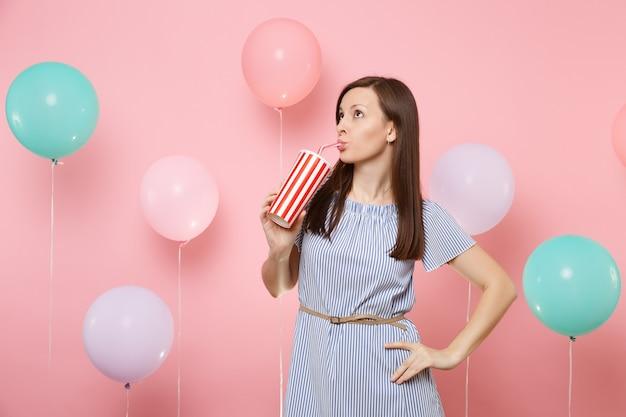 Ritratto di donna attraente che indossa un abito blu che beve cola o soda da una tazza di plastica su sfondo rosa pastello con mongolfiere colorate. festa di compleanno, concetto di emozioni sincere della gente.