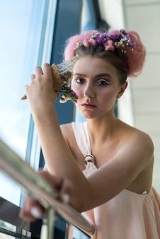 Ritratto di donna attraente con acconciatura e trucco vicino alla finestra