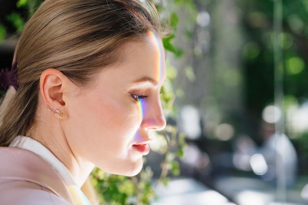 Ritratto di una donna attraente con la luce dell'arcobaleno sul viso