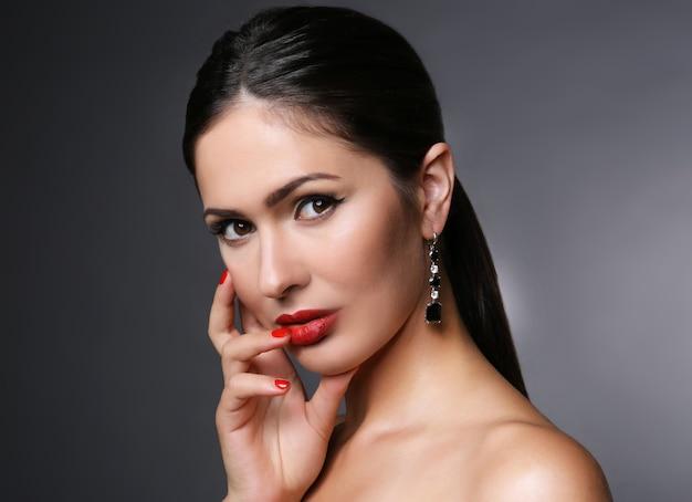 Ritratto di donna attraente con labbra rosse su sfondo grigio