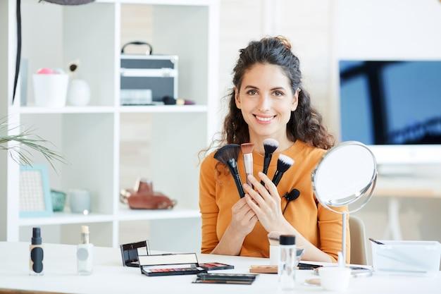 Ritratto di attraente giovane donna adulta seduta al tavolo tenendo vari pennelli per il trucco