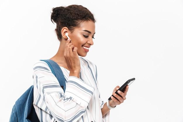 Ritratto di una giovane donna africana attraente che porta zaino in piedi isolato su un muro bianco, ascoltando musica con auricolari wireless, tenendo il telefono cellulare
