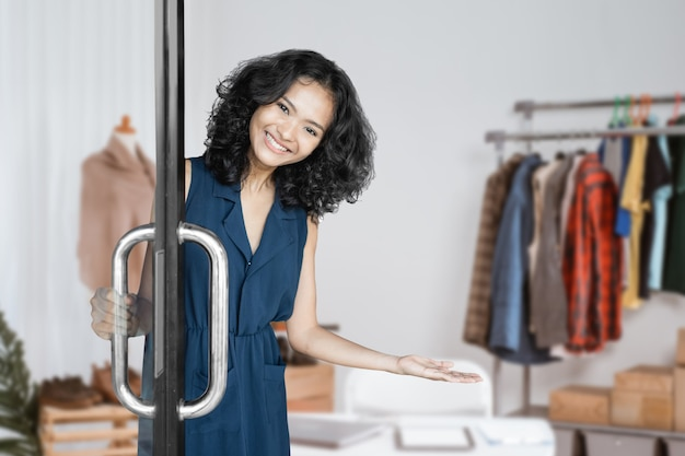 Ritratto di attraente giovane donna asiatica che accoglie il cliente nel suo piccolo negozio