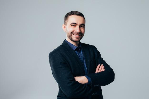 Ritratto di attraente giovane uomo d'affari in tuta in piedi con le braccia incrociate su sfondo grigio chiaro