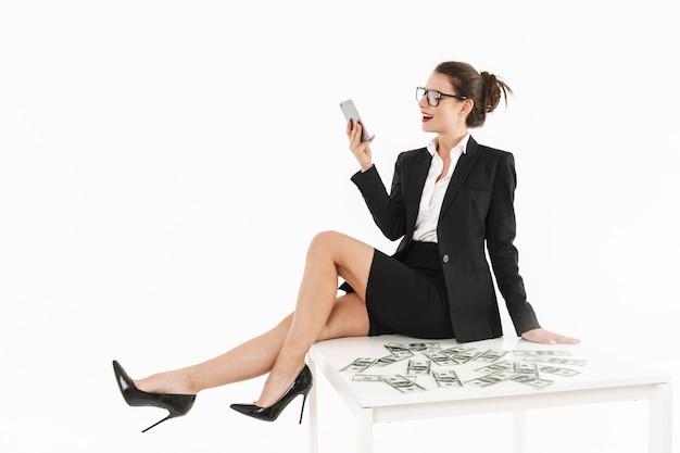 Ritratto di una giovane donna d'affari attraente in abiti formali seduta sulla scrivania isolata su un muro bianco, parlando al cellulare
