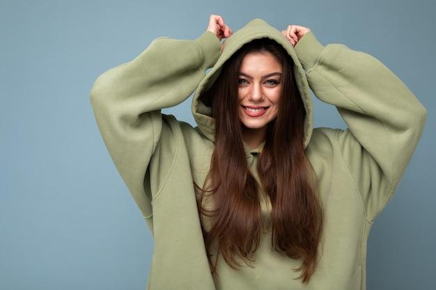 Ritratto di modello di donna bruna sorridente caucasica giovane attraente in felpa con cappuccio cachi alla moda e cappuccio da portare isolato su priorità bassa blu con lo spazio della copia. concetto positivo.