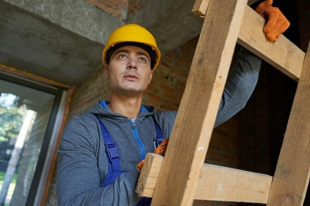 Ritratto di giovane costruttore maschio attraente in elmetto che guarda lontano salendo la scala