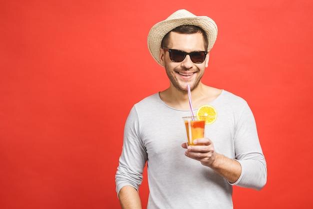 Ritratto di giovane attraente in cappello e occhiali da sole in piedi e bere succo d'arancia su sfondo rosso