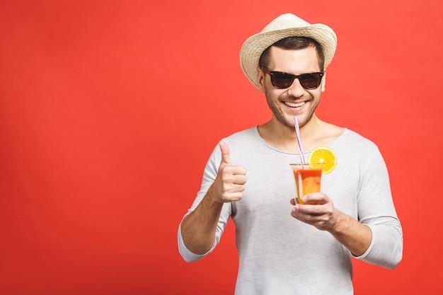 Ritratto di giovane attraente in cappello e occhiali da sole in piedi e bere succo d'arancia