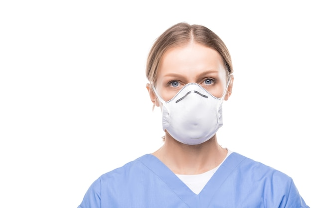 Ritratto di attraente giovane infermiera in maschera respiratoria e scrub in piedi