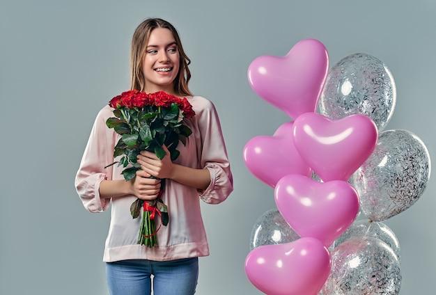 Ritratto di giovane donna attraente in camicetta è in piedi sul grigio con rose rosse in mano e palloncini.