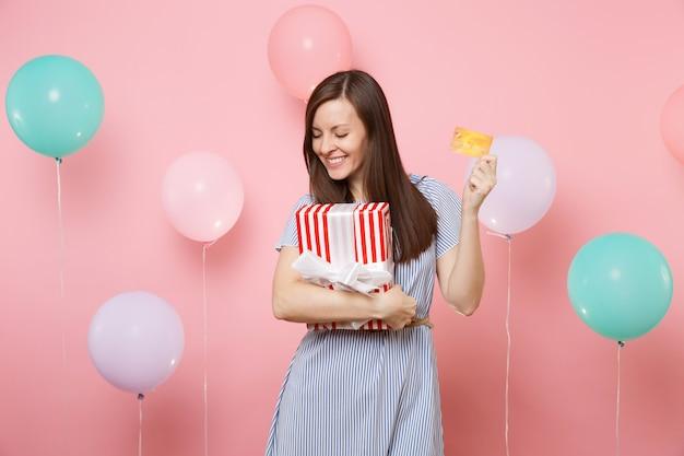Ritratto di giovane donna attraente in abito blu con carta di credito e scatola rossa con regalo presente su sfondo rosa pastello con mongolfiera colorata. festa di compleanno, persone sincere emozioni.
