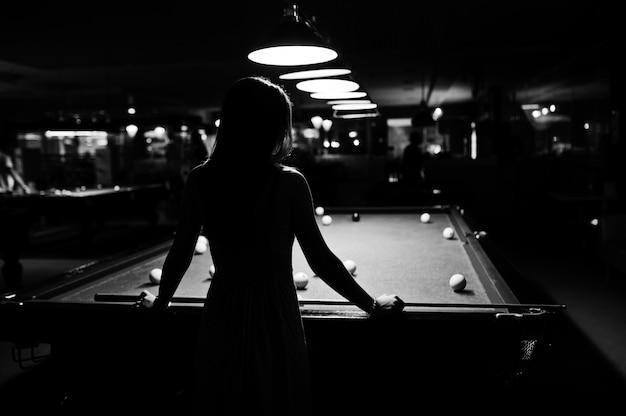Ritratto di una giovane donna attraente in abito giocando a biliardo. foto in bianco e nero.