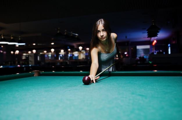 Ritratto di una giovane donna attraente in abito giocando a biliardo.
