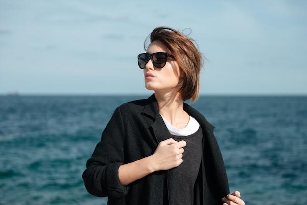 Ritratto di giovane donna attraente in occhiali da sole in piedi vicino al mare