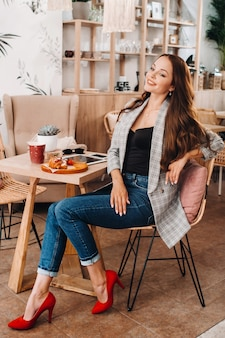 Ritratto di una giovane donna attraente che è seduta in un caffè. cafe stile di vita urbano. ritratto casuale.
