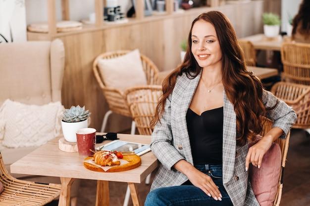 Ritratto di una giovane donna attraente che è seduta in un caffè.