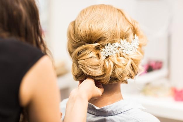 Ritratto di giovane donna attraente con bella acconciatura e accessorio per capelli alla moda, vista posteriore.