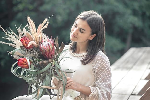 Ritratto di una giovane donna attraente con un mazzo di fiori esotici