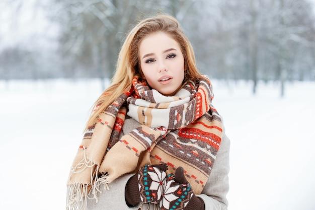 Ritratto di una giovane donna attraente con gli occhi marroni con una bella sciarpa vintage di lana alla moda in guanti in un cappotto alla moda