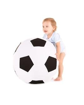 Ritratto di bambino con pallone da calcio su muro bianco