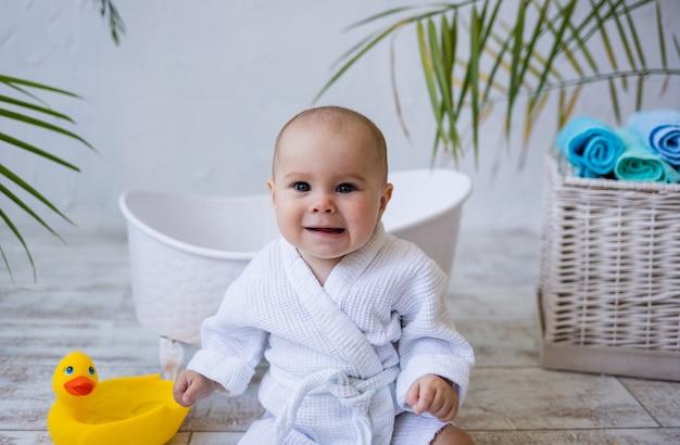 Ritratto di una bambina in una veste bianca seduta vicino a un bagno su uno sfondo bianco con un posto per il testo. cura dei bambini