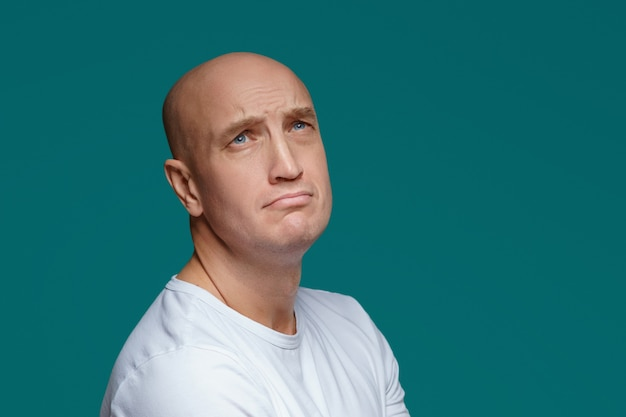 Ritratto di un uomo adulto calvo con un'espressione triste in una maglietta bianca