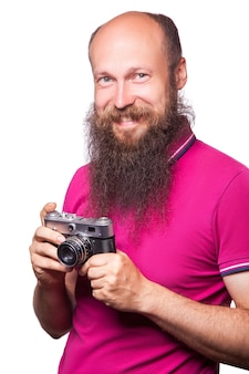Il ritratto di un uomo calvo e barbuto fotografo con una maglietta rosa che tiene in mano una macchina fotografica classica. isolato su sfondo bianco. girato in studio.
