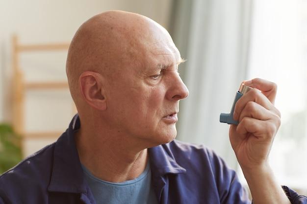 Ritratto di uomo anziano calvo utilizzando inalatore per l'asma o problemi respiratori in interni domestici Foto Premium