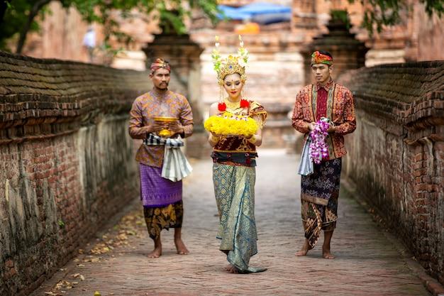 Il ritratto dei ballerini balinesi sta tenendo l'oblazione in abbigliamento tradizionale al portone di bali