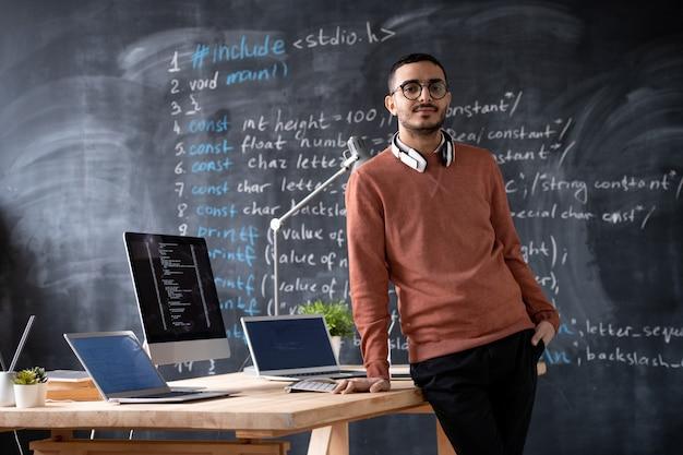 Ritratto di barbuto sviluppatore di software arabo con cuffie wireless intorno al collo in piedi alla scrivania con i computer in ufficio