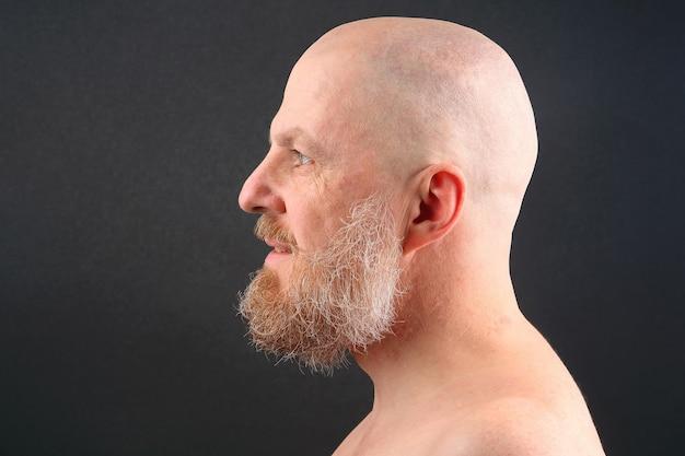 Ritratto di un uomo barbuto e calvo di profilo