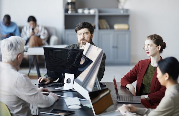 Ritratto di manager barbuto che ascolta i colleghi durante la riunione al tavolo all'interno dell'ufficio bianco, spazio copia