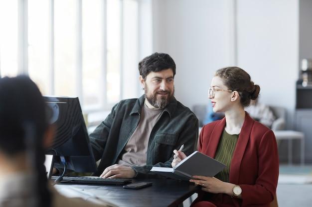 Ritratto di un manager barbuto che parla con una collega durante la riunione al tavolo nell'interno dell'ufficio bianco