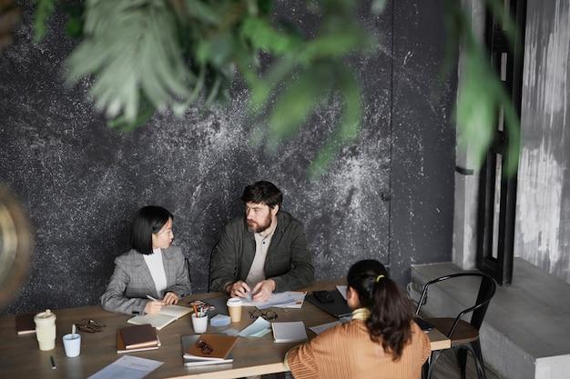 Ritratto di uomo d'affari barbuto che parla con colleghe durante la riunione al tavolo in un ufficio grigio minimo, spazio copia